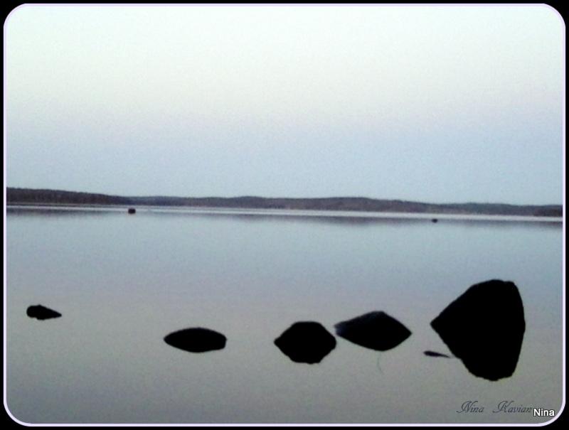 En stämningsfull sjöbild, den tycker jag blev vacker och lugn. Stenarna avtecknar sig tydligt mot den blanka vattenytan, utan krusningar. Horisonten på andra sidan sjön.